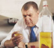 Depressed man looking at drink with bottle